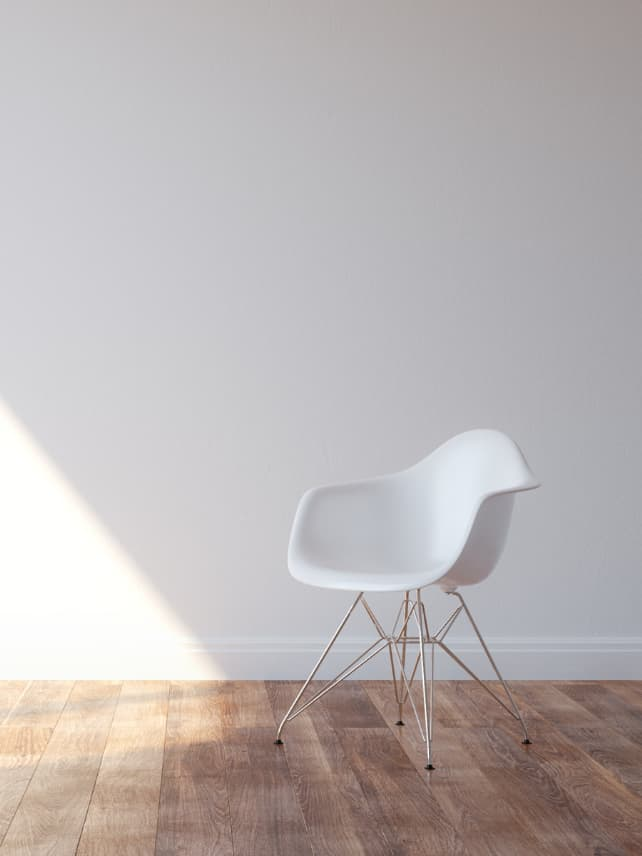 White minimalist style chair in an empty room with white walls and a wood floor.
