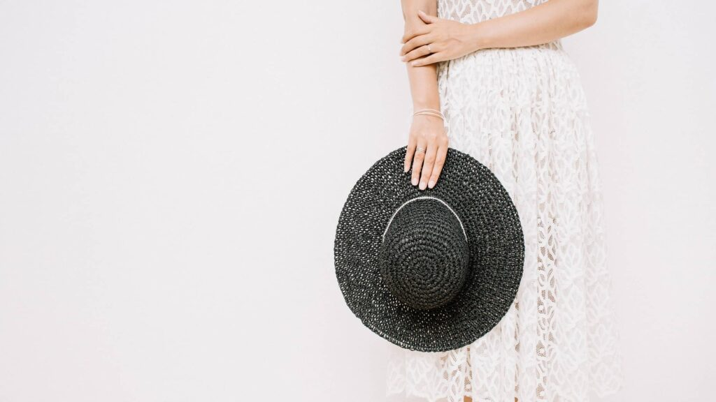 A waist down image of a standing woman wearing a lace dress holding a black straw hat