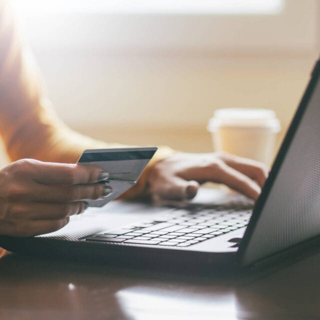 A lady sitting in front of a laptop holding credit cards while online shopping
