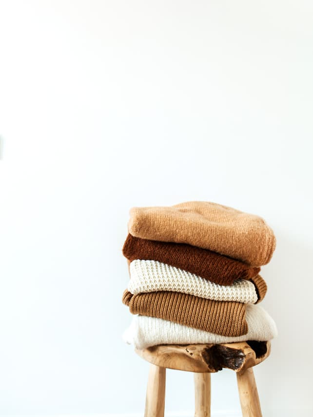 Stack of warm, autumn coloured sweaters in brown and orange hues on a wooden stool.