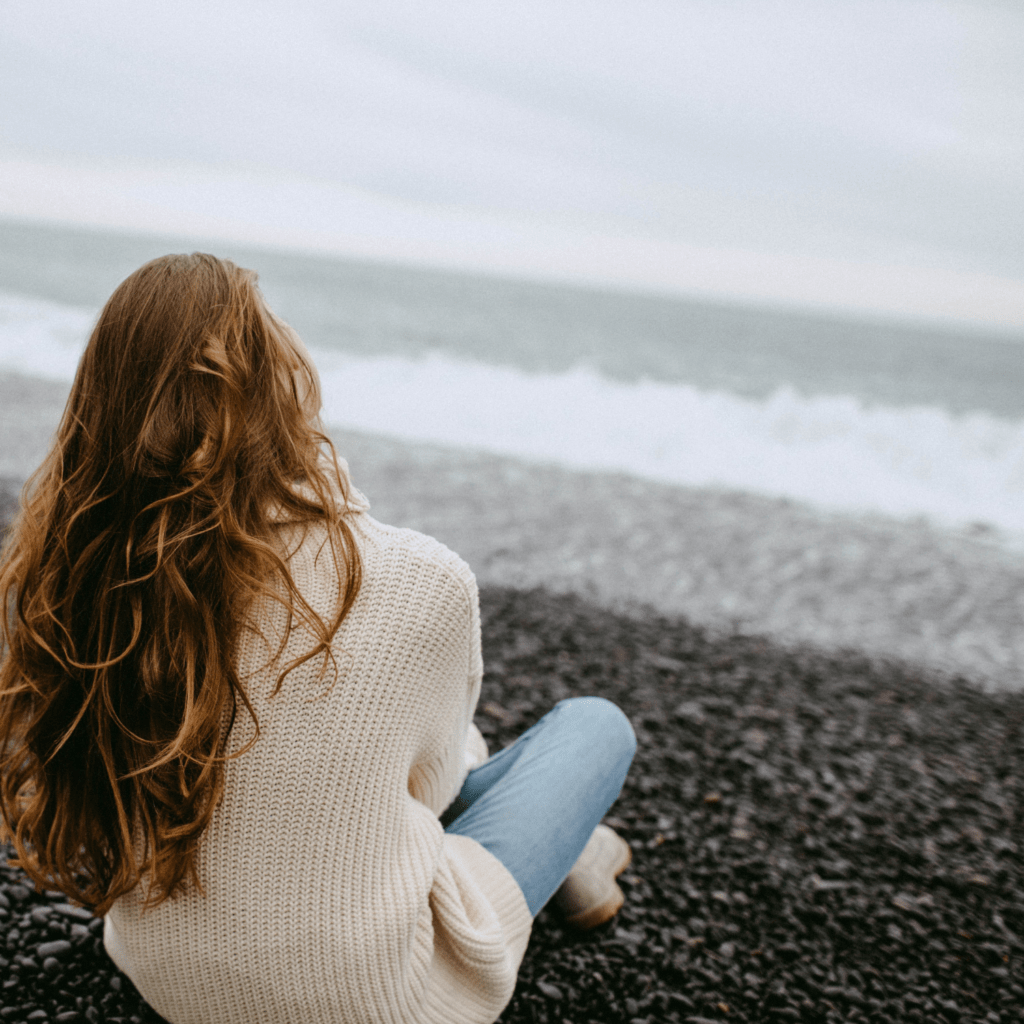 A woman sitting on a beach watching the waves on a cloudy, dreary day.