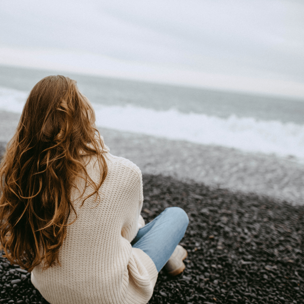 A woman sitting on a beach watching the waves on a cloudy, dreary day
