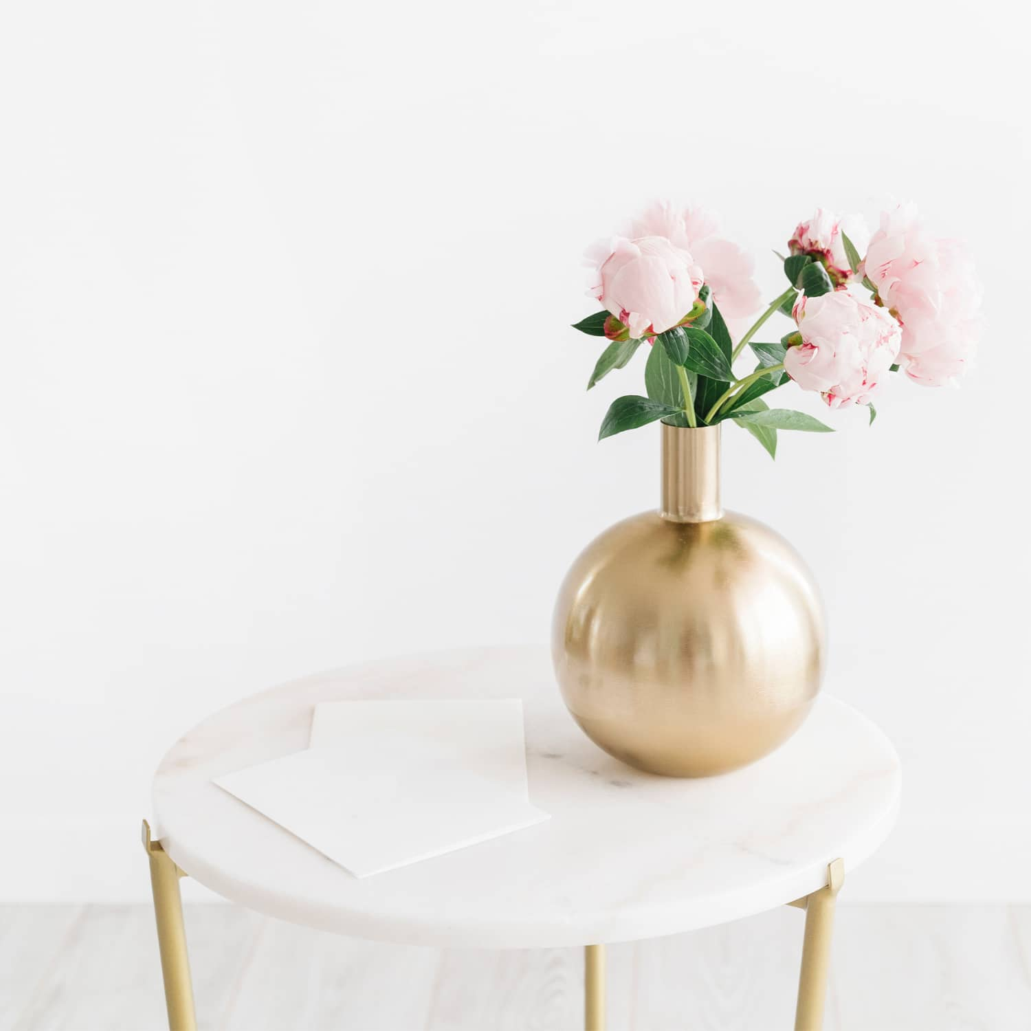 A side table with a gold vase holding pink peonies and a note pad on it