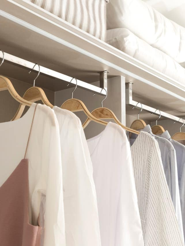 A white minimalist closet with a selection of neutral tops hanging neatly on wooden hangers.