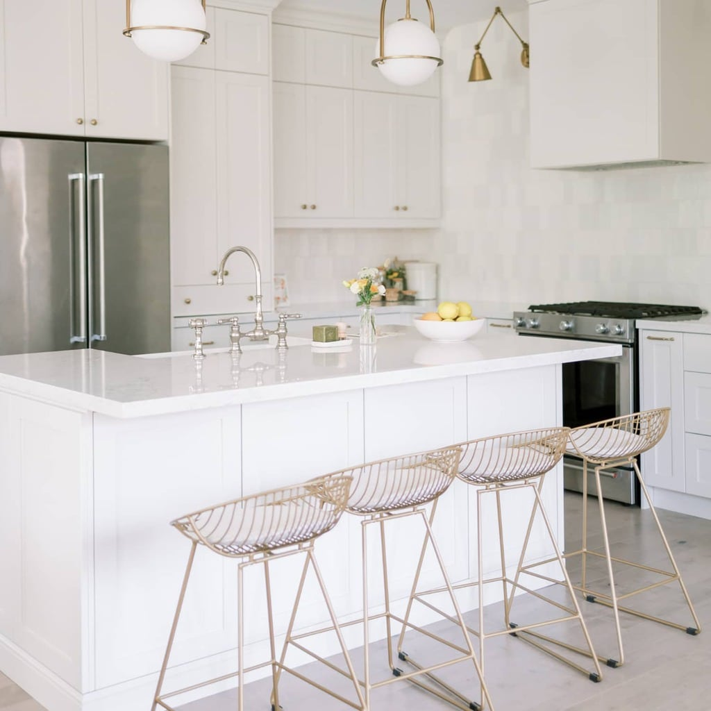 A white minimalist kitchen with gold bar stools.