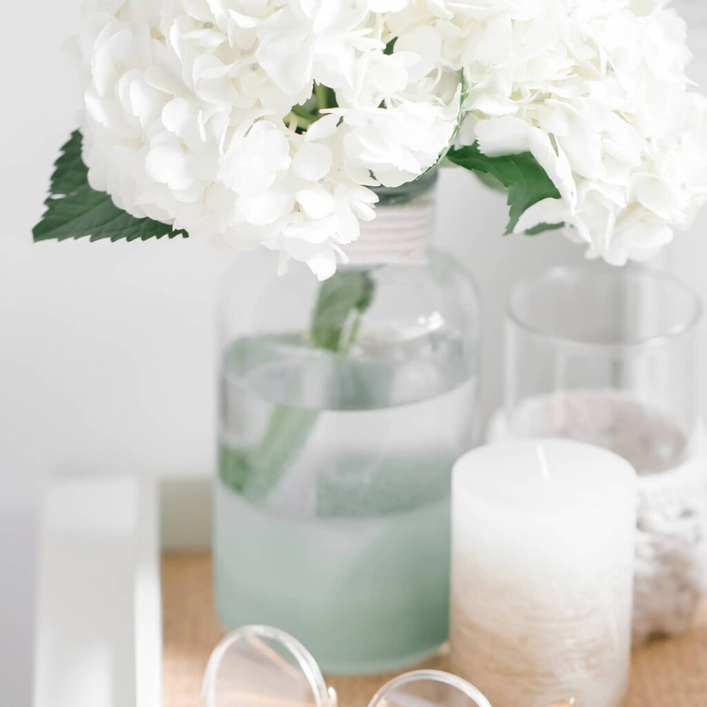 A tray holding a pair of glasses, a candle, and a vase holding white flowers.