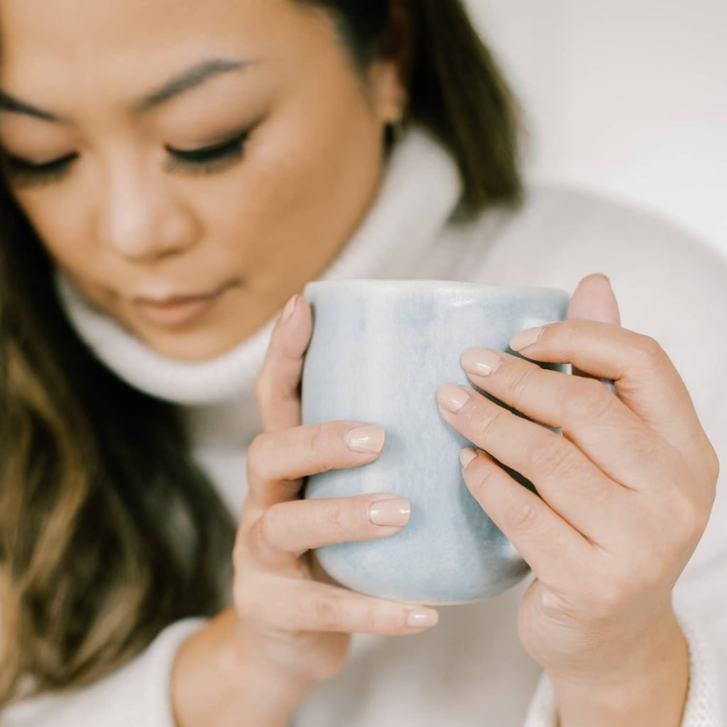A closeup of a woman wearing a cream turtleneck and holding a light blue mug while looking down.