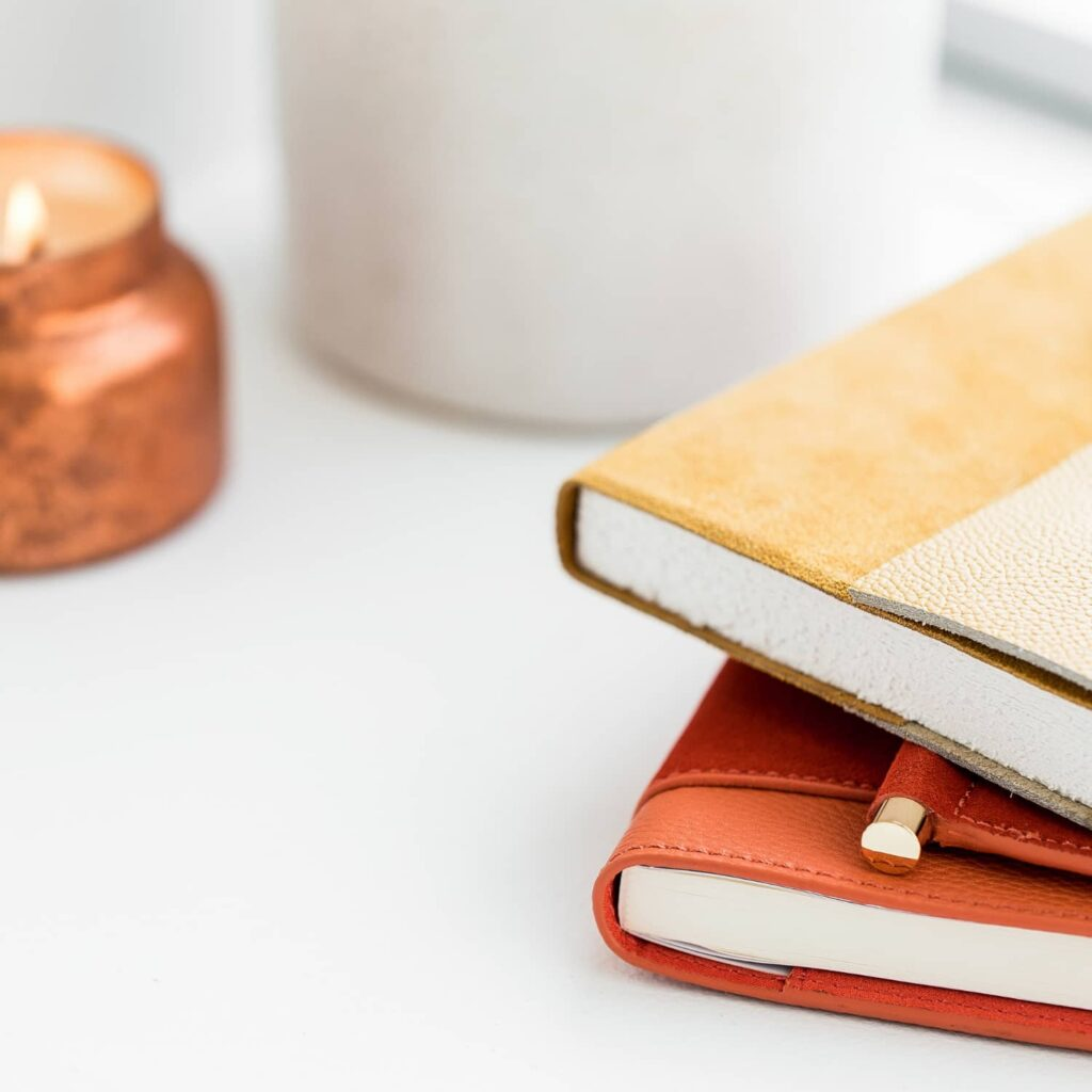 2 leather bound journals - 1 yellow and 1 orange - and a bronze coloured candle holder against a white background.