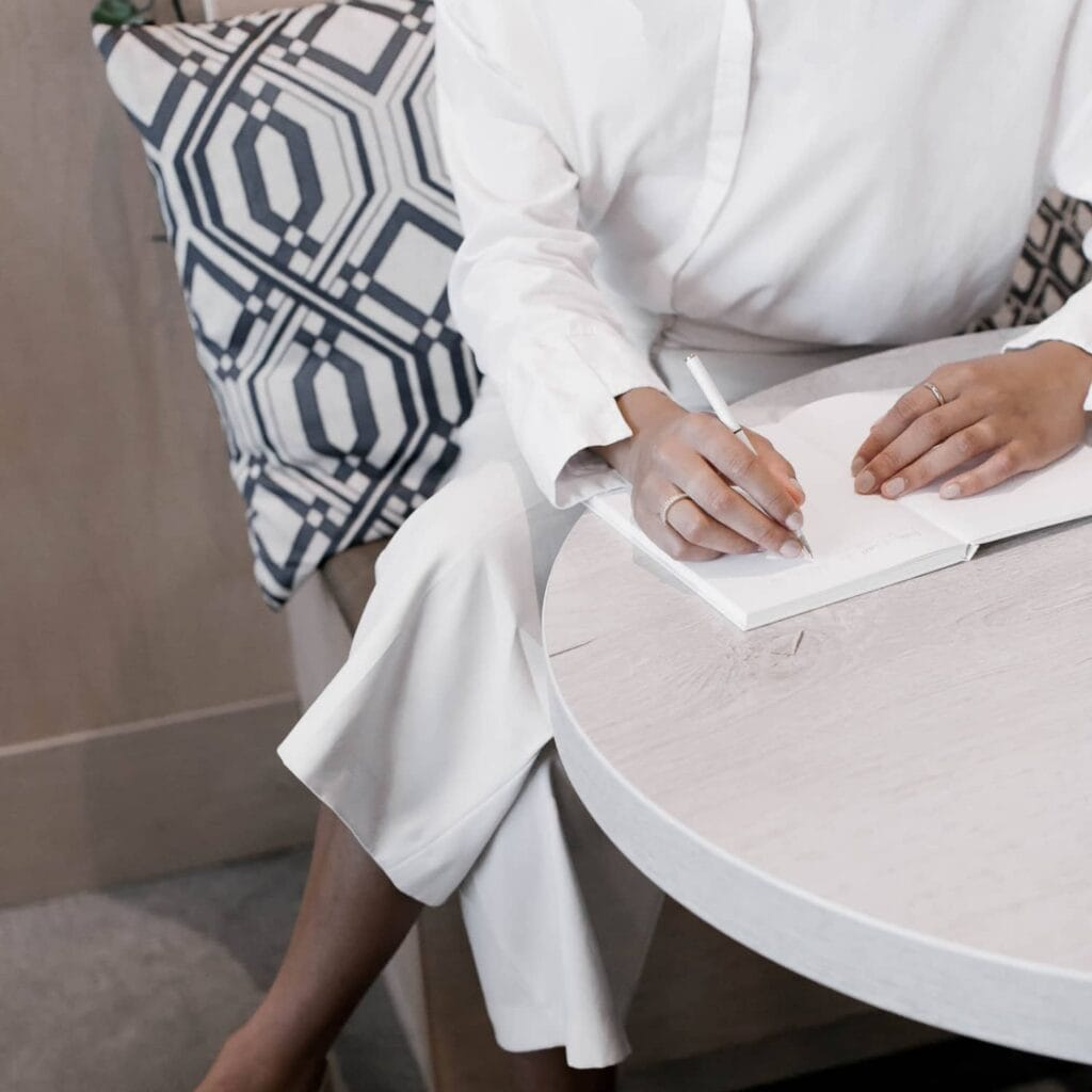A woman dressed in white sitting at a table writing in an open journal