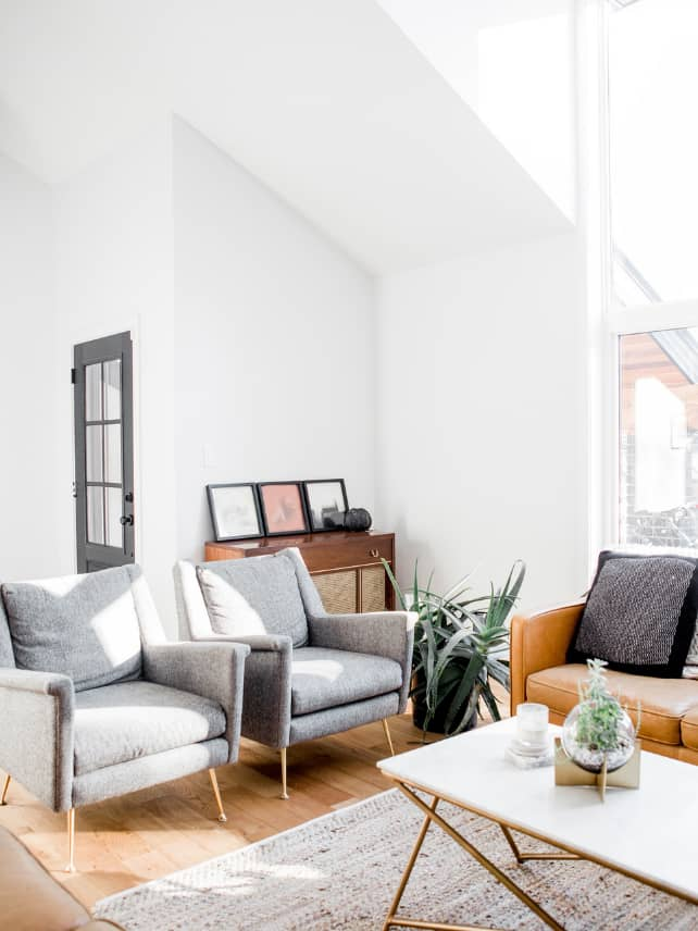 A minimalist living room with a mustard colored sofa, 2 grey chairs, a plant, a low table with a vase and candle.
