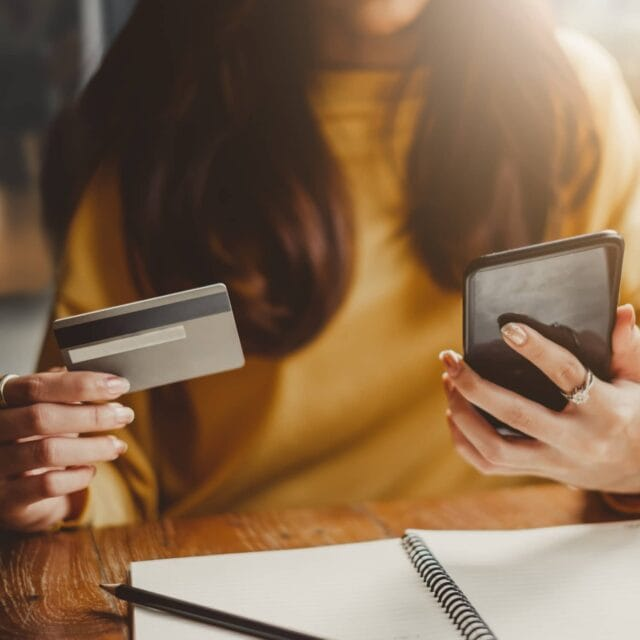 A close up of a woman holding a credit card while looking at a cell phone.