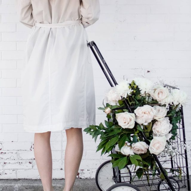 A woman facing away from the camera wearing a light trench coat standing beside a basket of flowers against a brick wall