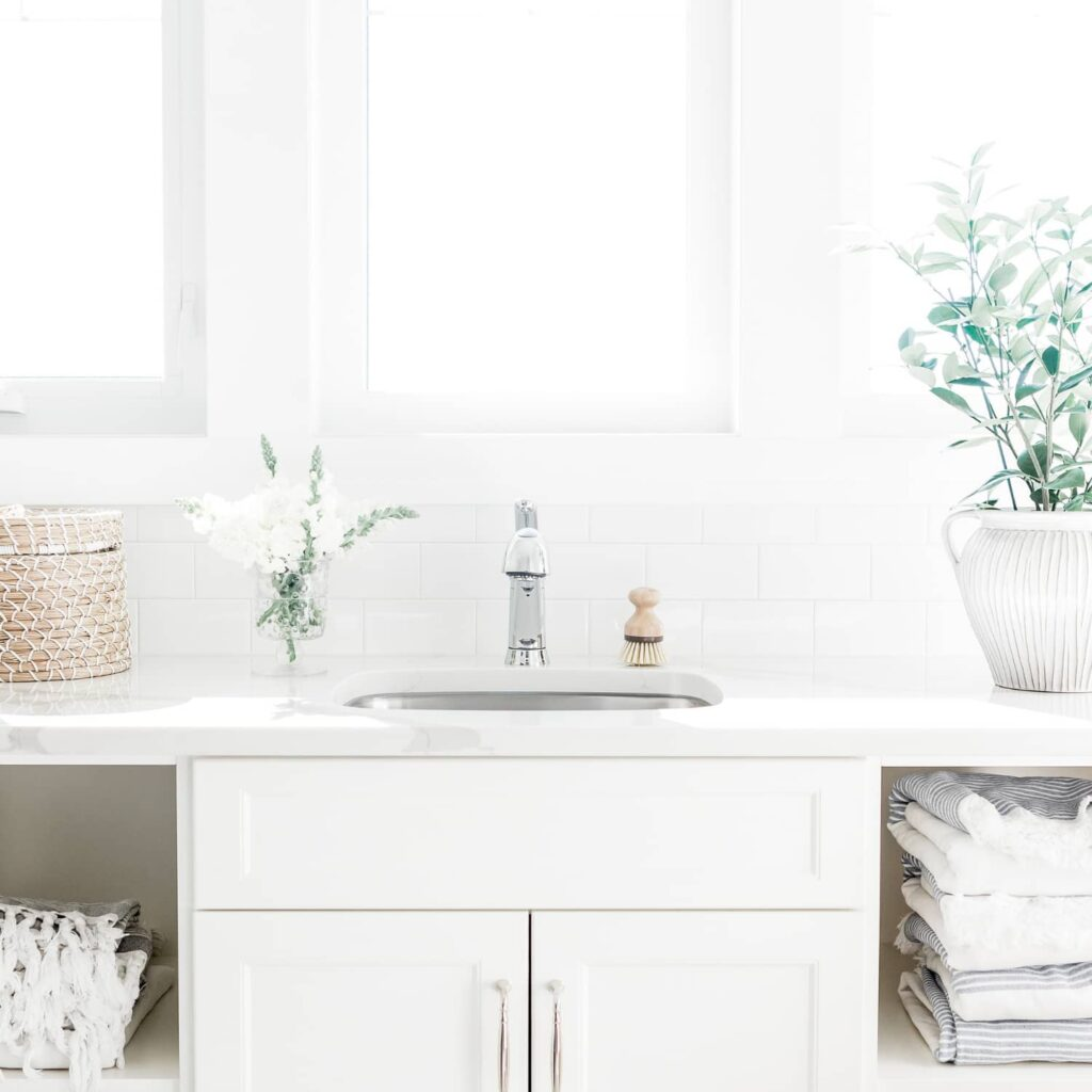A minimalist laundry room with white cabinets, folded grey striped linens, a small basket, and a plant against a white background.