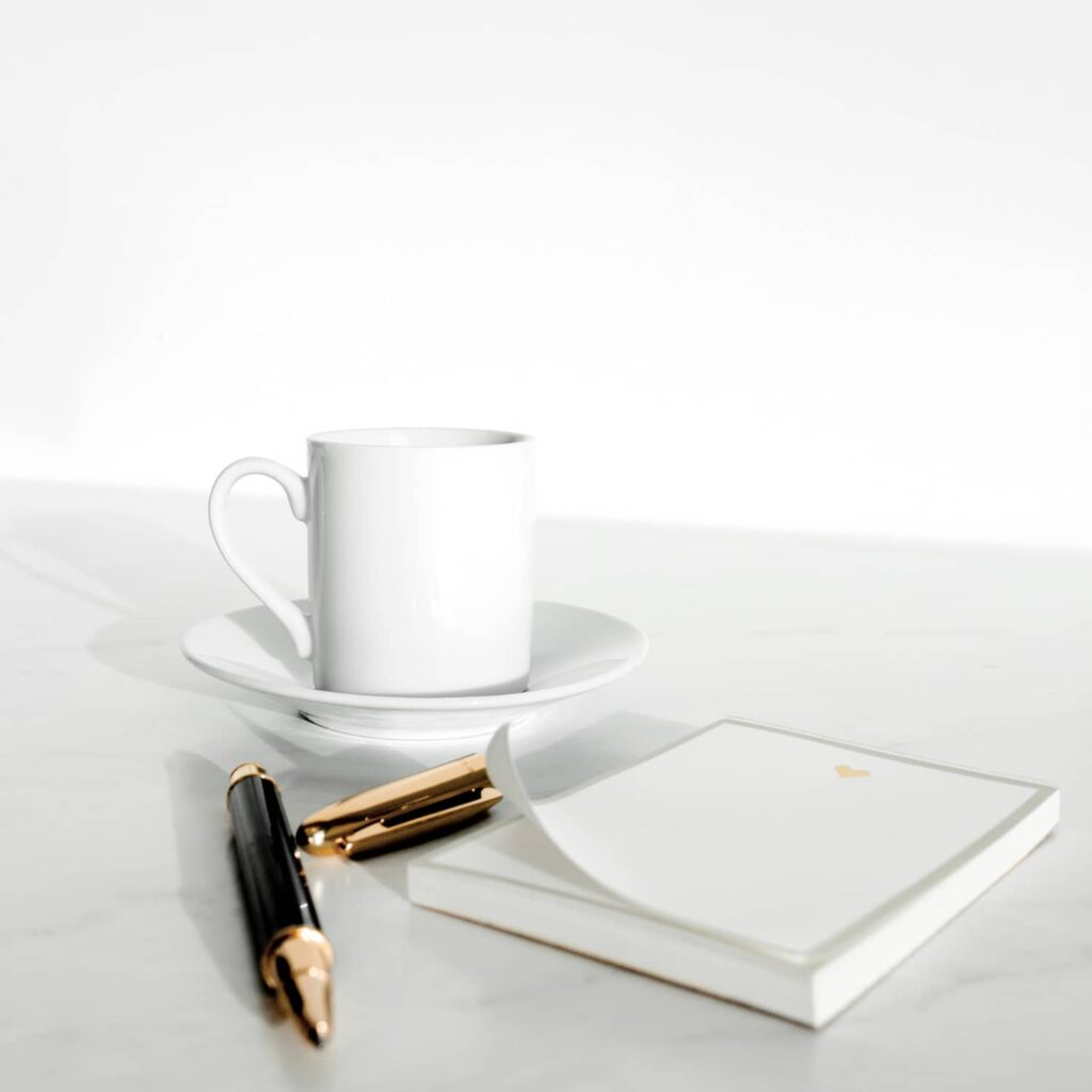 A coffee cup, note pad, and pen in the background.