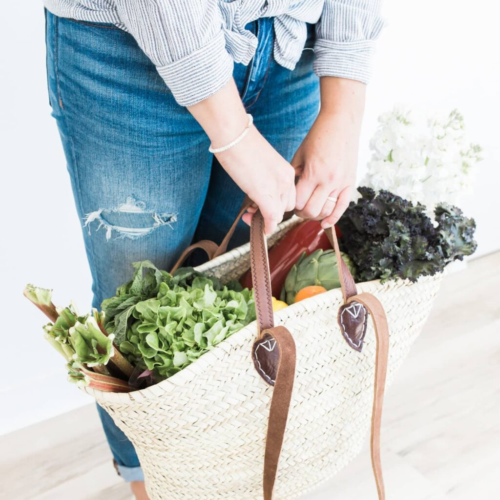 A woman wearing blue jeans and a stripped button up top holding a wicker bag full of fresh vegetables.