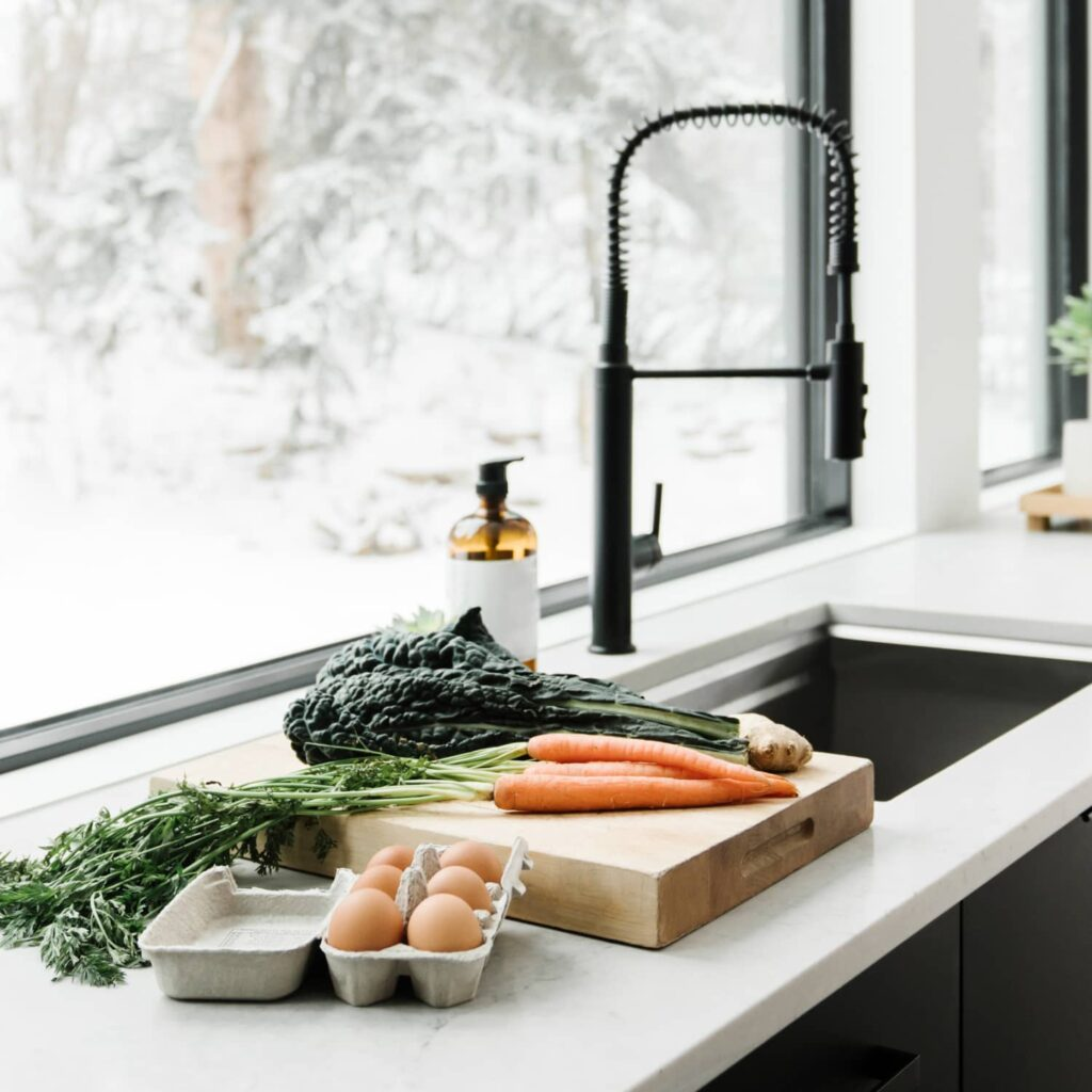 A minimalist kitchen with black cupboards, here is a wooden cutting board with carrots, kale, and ginger on a white countertop, a carton of brown eggs, a sink, and a black faucet all in front of a large window.