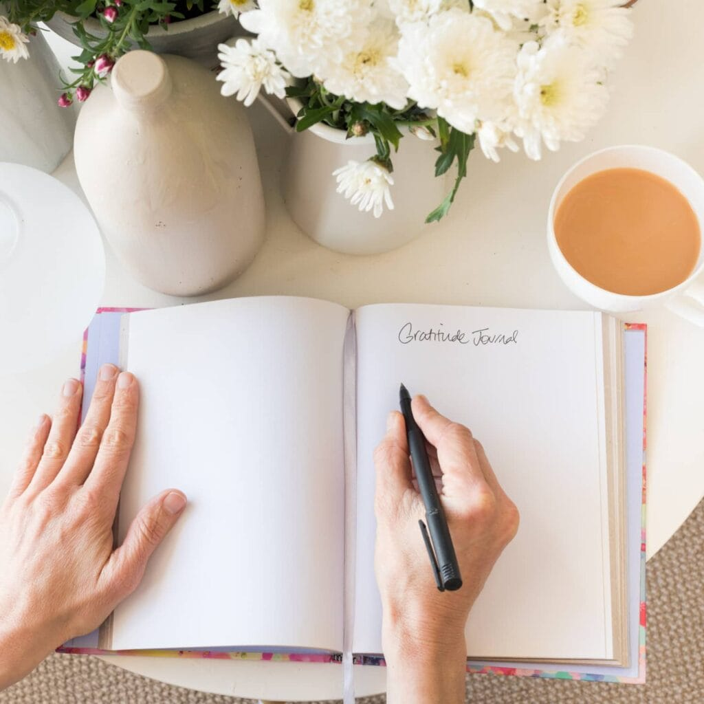 An image of a woman's hand writing in an open gratitude journal, a vase of flowers, and a cup of coffee in the background.