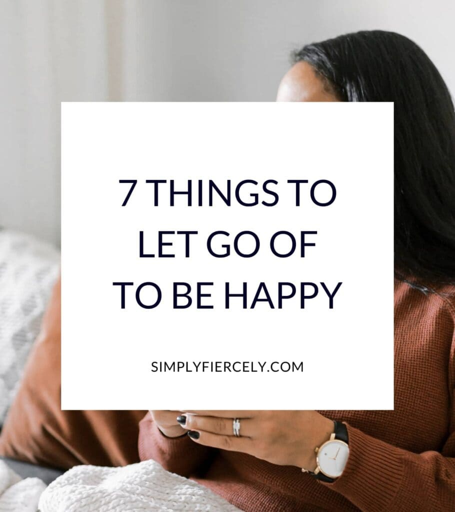 """""""7 Things To Let Go Of To Be Happy"""" in a white box with a woman wearing a taupe long sleeved top holding a cup of coffee and sitting on a sofa in the background."""