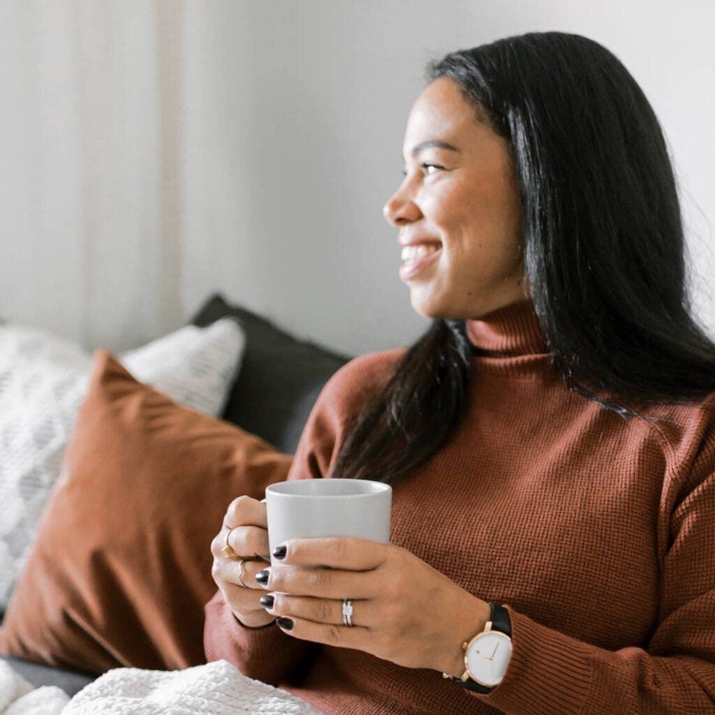 A smiling woman wearing a taupe turtleneck holding a cup of coffee sitting on a sofa.