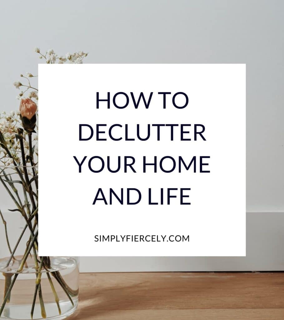 """A white box with the text: """"How to declutter your home and life."""" In the background is a glass vase with delicate flowers, sitting on a wood floor against a white wall."""