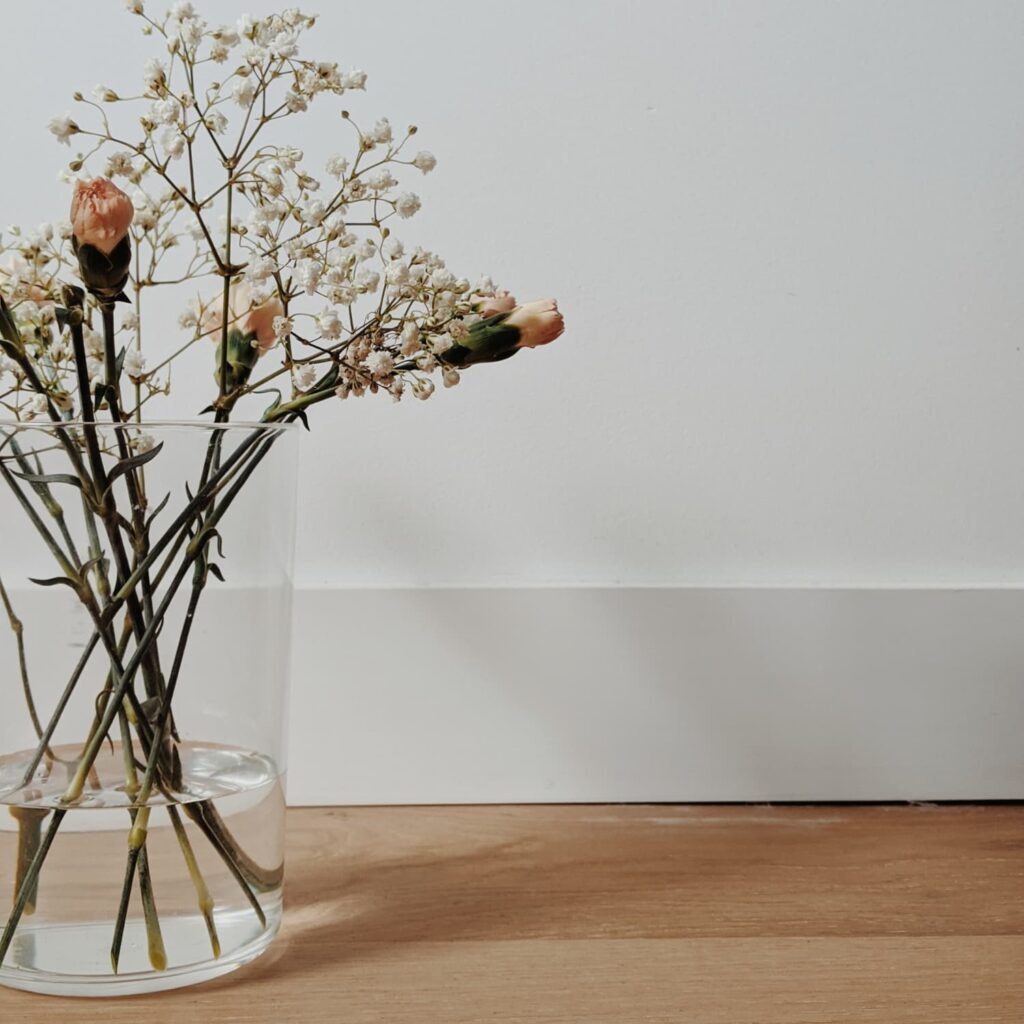A simple glass vase with delicate flowers on a wood floor against a white background.