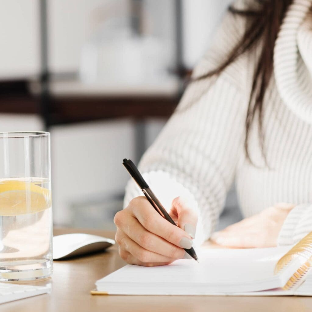 A woman writing in a journal with a glass of lemon water on the table beside her.