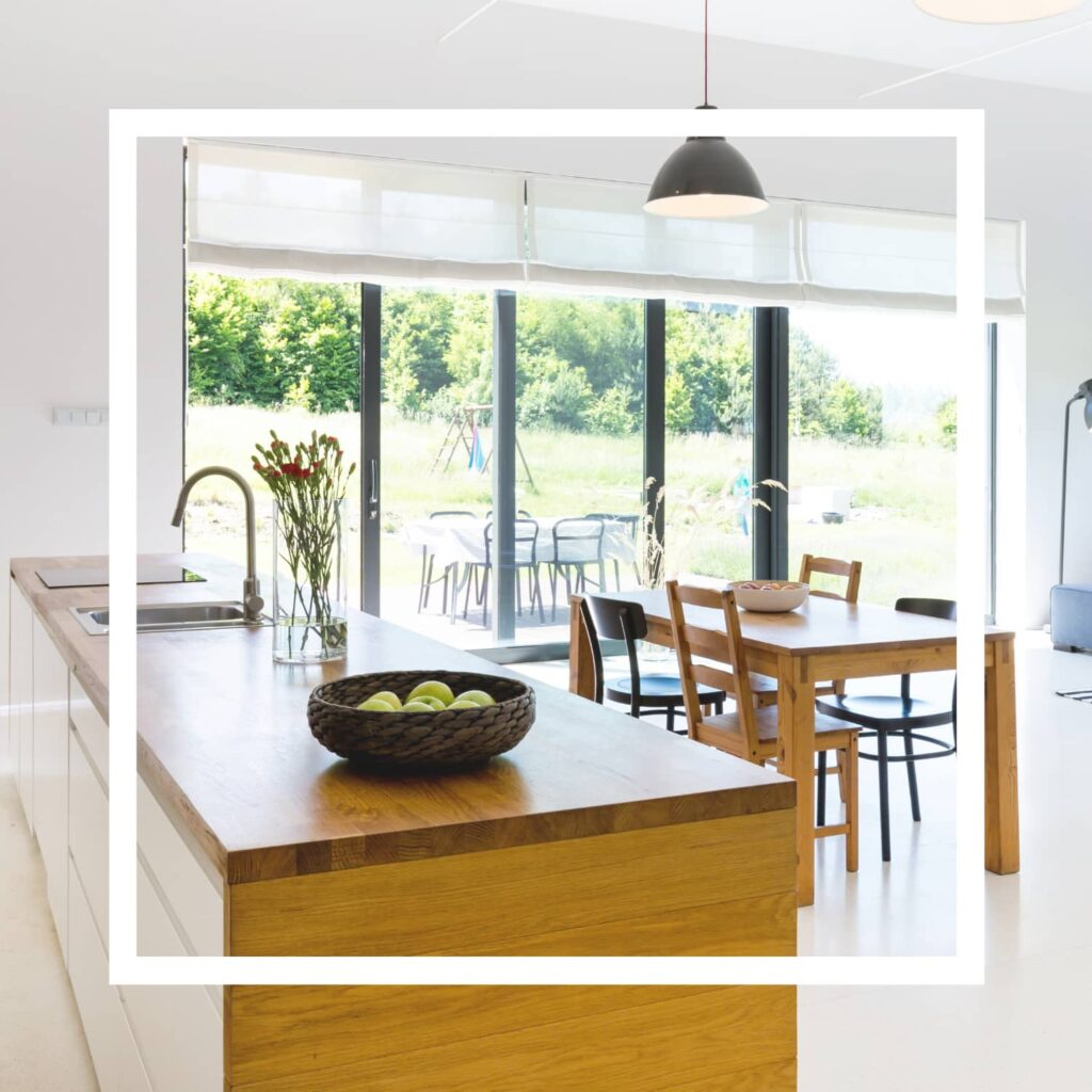 A kitchen with a clutter-free wood tone island, a wooden dining room table and a large window looking out on a large yard.