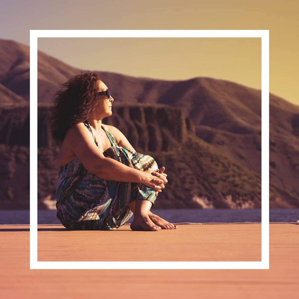 An image of a woman sitting on the sand with mountains in the background.