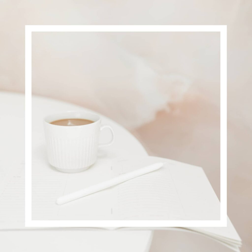 A white square overlay with an open blank journal, a pen, and a cup of coffee on a white table in the background.