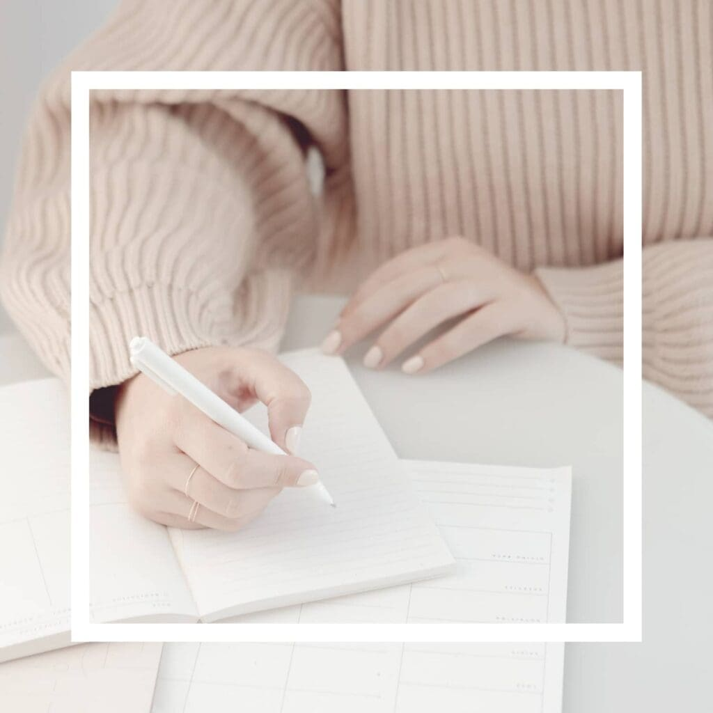 A white square overlay with an image of a woman wearing a pale pink sweater holding a white pen writing in a journal in the background.,