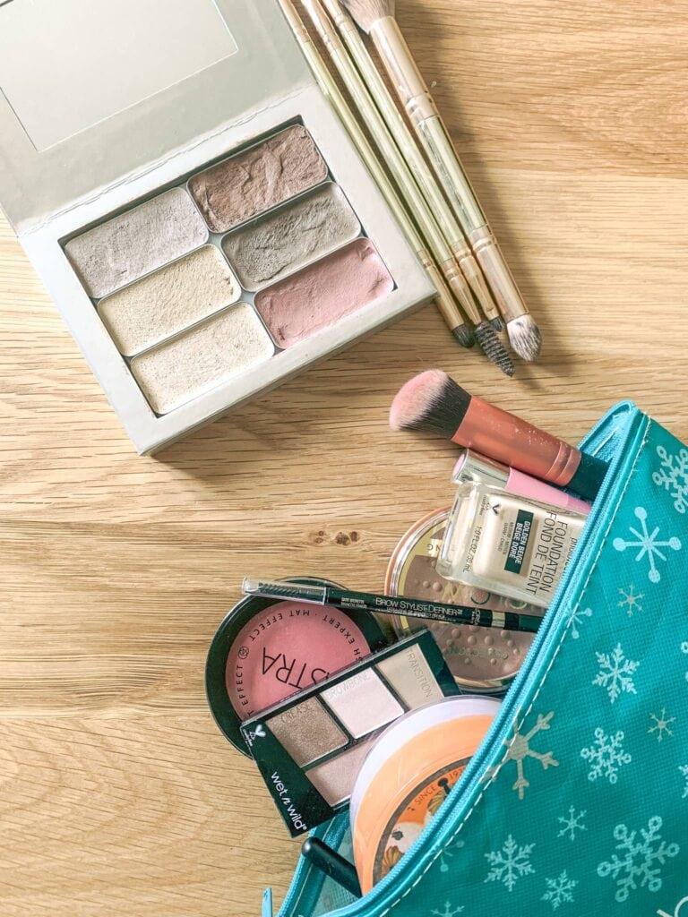 An assortment of cosmetics in an open makeup bag on a wooden background